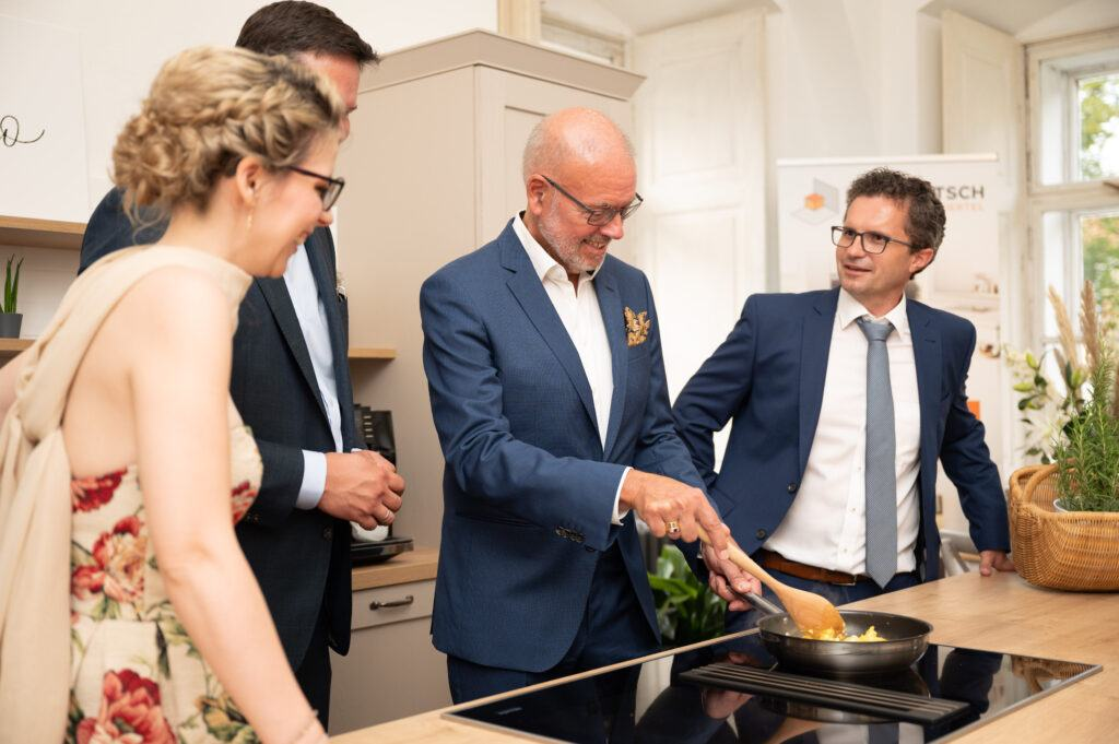 Ehrengaeste Lukas Mandl Schlossbesitzer Dr Paul Drobec und Buergermeister Christoph Veit kochen gemeinsam mit Verena Pelikan eine Eierspeise bei der SchlossStudio Eroeffnung von Verena Pelikan im Schloss Coburg zu Ebenthal
