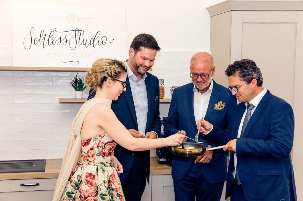 Die Ehrengaeste verkosten ihre selbst gemachte Eierspeise bei der SchlossStudio Eroeffnung von Verena Pelikan
