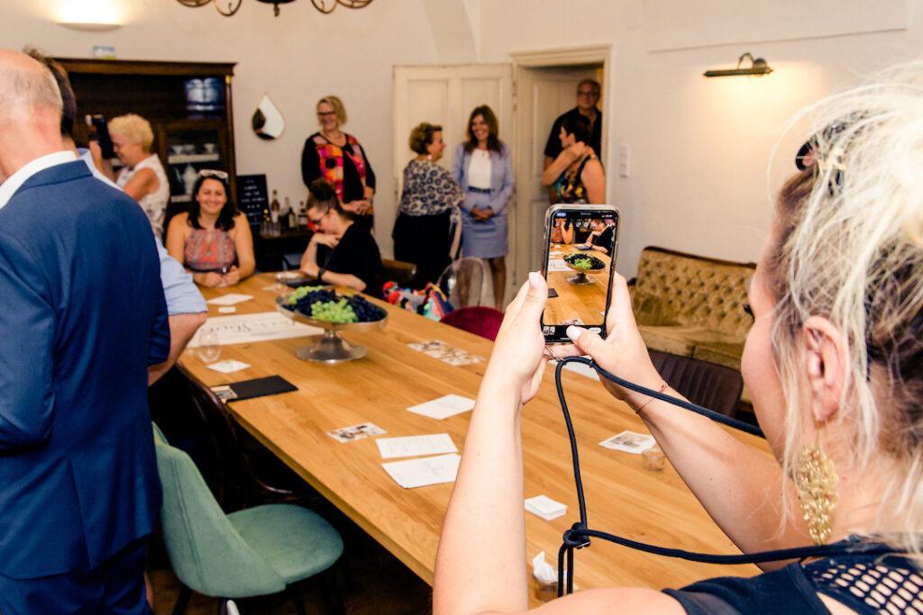 Gut gelaunte Gaeste im Seminarraum Holzbock werden mit dem Handy fotografiert bei der SchlossStudio Eroeffnung von Verena Pelikan im Schloss Coburg zu Ebenthal