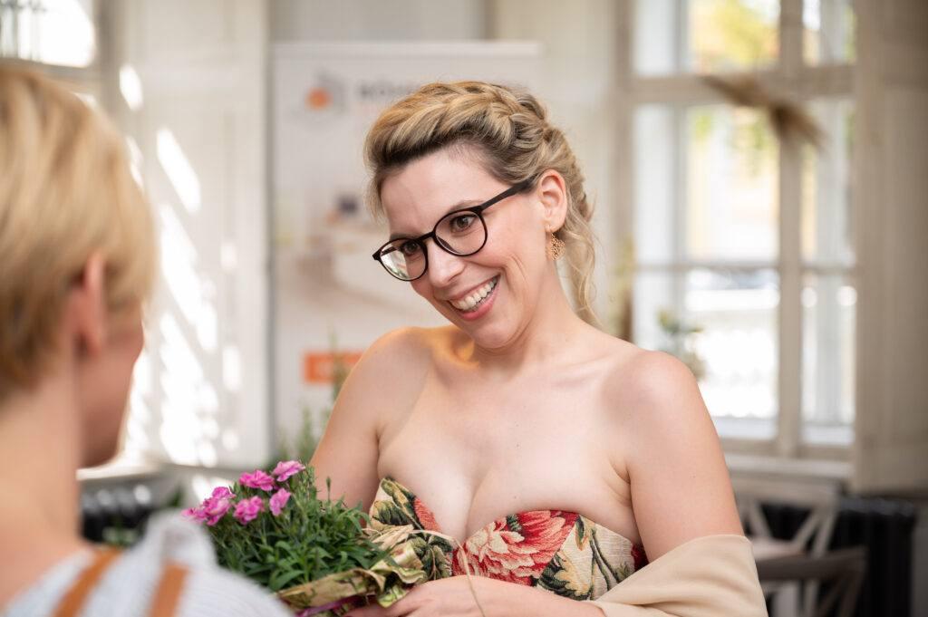 Verena Pelikan begruesst herzlich einen Gast in ihrem SchlossStudio bei der Eroeffnungsfeier