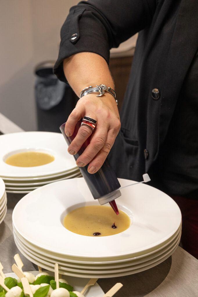 Anrichten der Apfel Sellerie Suppe beim Weihnachtskochen Event im Schauraum Wien fotografiert von Fotografin Verena Pelikan
