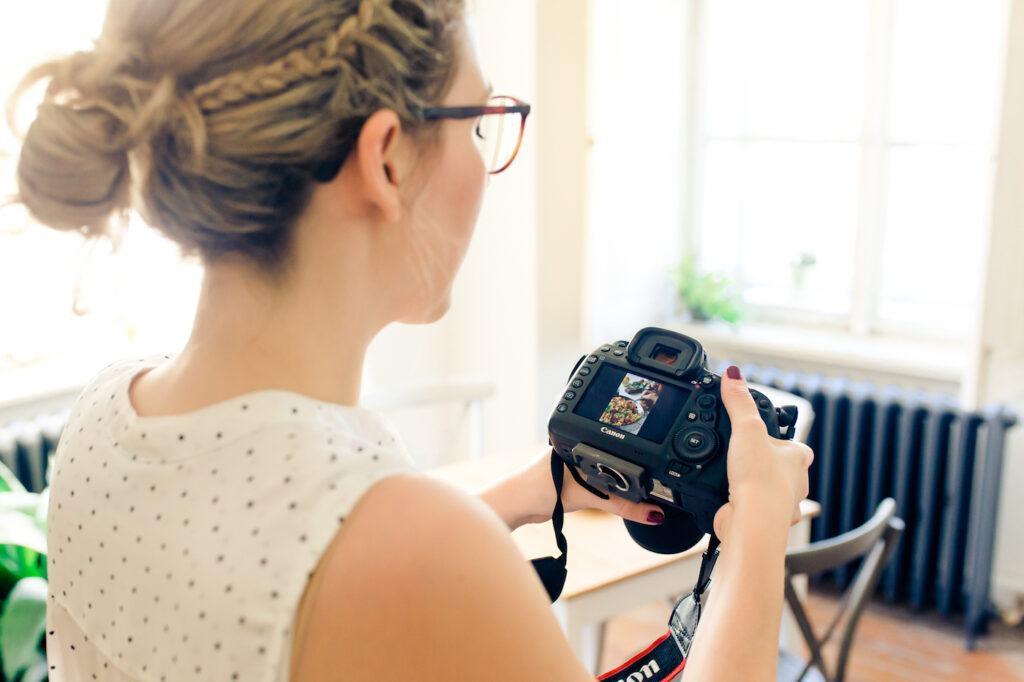 Foodfotografin Verena Pelikan beim Betrachten der von ihr aufgenommenen Fotos im Fotostudio SchlossStudio