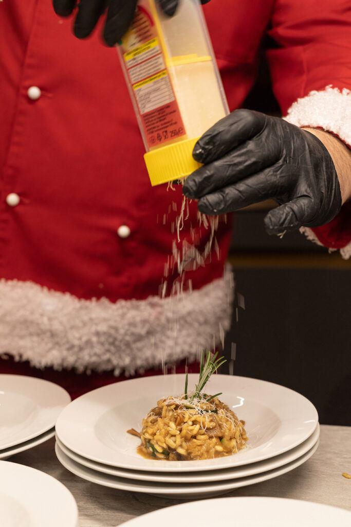 Parmesan wird beim Weihnachtskochen Event im Schauraum Wien ueber das Steinpilzrisotto gerieben und dabei von Fotografin Verena Pelikan fotografiert