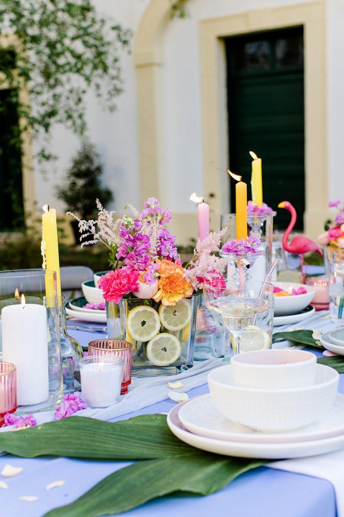 Bunte Blumendekoration und bunte Kerzen bei der Flamingo Gartenparty von Verena Pelikan im Kochstudio SchlossStudio