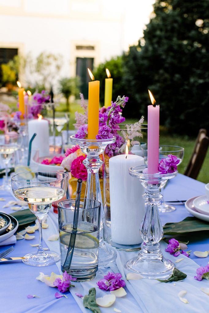 Bunte Kerzen und Blumen als Dekoration bei der Flamingo Party von Verena Pelikan im Garten vom Kochstudio SchlossStudio im Weinviertel