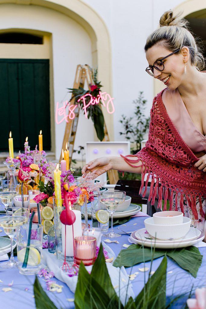 Gastgeberin Verena Pelikan begutachtet die Flamingo Deko von Dekoprofi Manuela Simek fuer ihre Gartenparty im Kochstudio SchlossStudio im Weinviertel